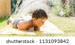 boy cooling down with garden... | Shutterstock . vector #1131093842