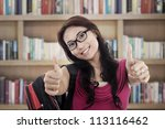 Portrait of asian college student showing thumbs-up. shot in the library - stock photo