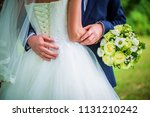 bride holds bouquet and stands... | Shutterstock . vector #1131210242