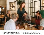 smiling young waitress taking... | Shutterstock . vector #1131220172