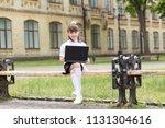 girl schoolgirl with laptop on... | Shutterstock . vector #1131304616