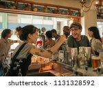 smiling bar patron ordering... | Shutterstock . vector #1131328592