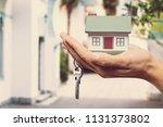 businessman holding house model ... | Shutterstock . vector #1131373802