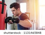 handsome man in boxing gloves... | Shutterstock . vector #1131465848
