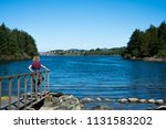 woman watching over a lake in... | Shutterstock . vector #1131583202