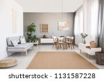 grey sofa near white chairs at... | Shutterstock . vector #1131587228