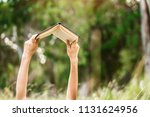 hands raising a book up to read | Shutterstock . vector #1131624956