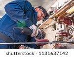 a young man welder in a blue t... | Shutterstock . vector #1131637142