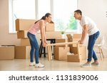 young couple carrying table in... | Shutterstock . vector #1131839006