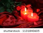 Stock photo burning heart shaped candles with red roses 1131840605