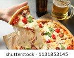 woman holding slice of... | Shutterstock . vector #1131853145