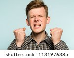 Small photo of anger rage and hatred. enraged infuriated man baring his teeth. portrait of a young guy on light background. emotion facial expression. feelings and people reaction concept.