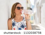 young woman drinking refreshing ... | Shutterstock . vector #1132038758