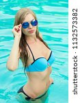 a girl in a blue swimsuit is... | Shutterstock . vector #1132573382