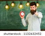 bearded hipster holds clock ... | Shutterstock . vector #1132632452