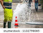 Small photo of road spurt water beside traffic cones