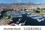 Small photo of Aerial photo of marina yacht club located at Palermo Sicily Italy showing streets on left and harbor on right furthermore showing the city center and mountains in background