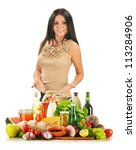 Young woman with variety of grocery products including vegetable, fruits, meat, dairy and wine - stock photo