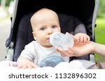 little kid sitting in stroller... | Shutterstock . vector #1132896302