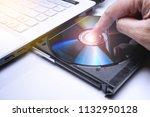 dvd disk on the white laptop... | Shutterstock . vector #1132950128