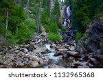 Water roaring down Fish Creek Falls lower falls in peak summer.