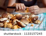 Woman Cleaning Wild Mushrooms...