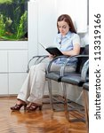 Full length of a young woman reading book in doctor's waiting room - stock photo