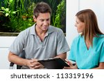 Female dentist with clipboard explaining something to man in clinic - stock photo