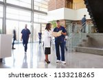 two healthcare workers talk in... | Shutterstock . vector #1133218265