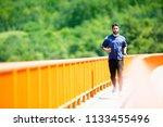handsome man running on bridge.  | Shutterstock . vector #1133455496