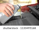 mechanic pouring oil into car... | Shutterstock . vector #1133495168