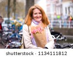 girl holding a bouquet of... | Shutterstock . vector #1134111812