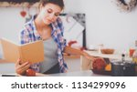 young woman reading cookbook in ... | Shutterstock . vector #1134299096