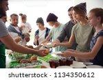 volunteers serving food for... | Shutterstock . vector #1134350612