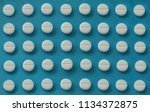 rows of white pills on a blue... | Shutterstock . vector #1134372875