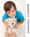 Young boy with his doggy playing on the floor - top view - stock photo