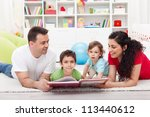 Young family story time with the kids - laying on the floor together - stock photo