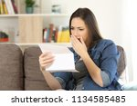 sad woman reading bad news in a ... | Shutterstock . vector #1134585485