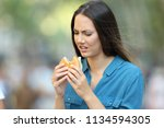 disgusted woman eating a burger ... | Shutterstock . vector #1134594305