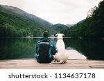 man sitting with a dog on dock... | Shutterstock . vector #1134637178