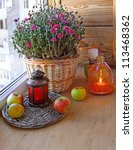 Bunch of pink chrysanthemums in a basket and a lantern on a balcony - stock photo