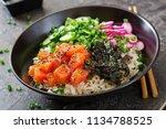 Small photo of Hawaiian salmon fish poke bowl with rice, radish,cucumber, tomato, sesame seeds and seaweeds. Buddha bowl. Diet food