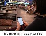 woman holding a smartphone... | Shutterstock . vector #1134916568