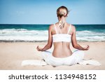 woman meditating on the beach ... | Shutterstock . vector #1134948152