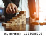 plan and strategy in business.risk concept.hand of man has piling up and stacking a wooden block.Businessman Building The Success.