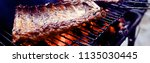 pork ribs on the grill cooking... | Shutterstock . vector #1135030445