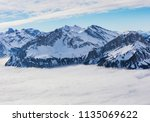 summits of the alps rising from ... | Shutterstock . vector #1135069622