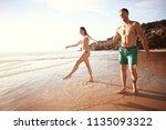 lovers run along the beach  ... | Shutterstock . vector #1135093322