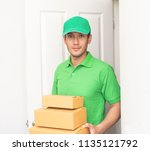 delivery man in green is... | Shutterstock . vector #1135121792