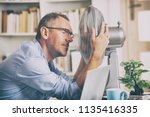 man suffers from heat while... | Shutterstock . vector #1135416335